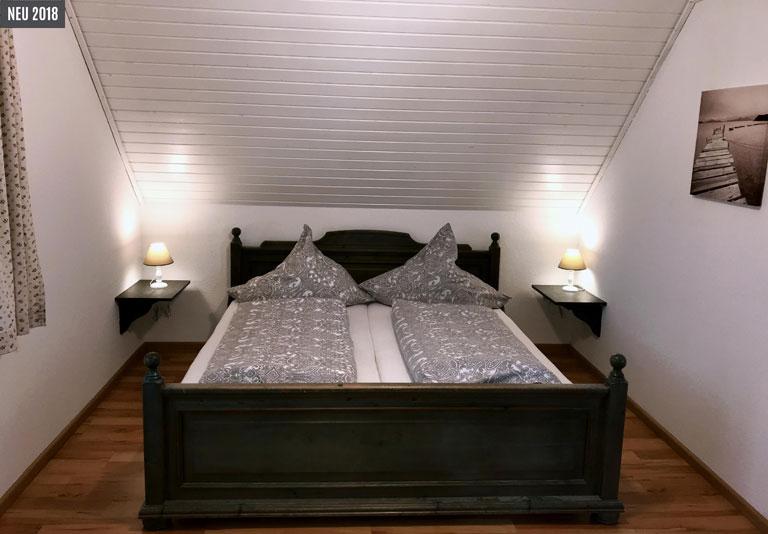 Doppelbett mit zwei Tischlampen und Parkettboden im Elternschlafzimmer